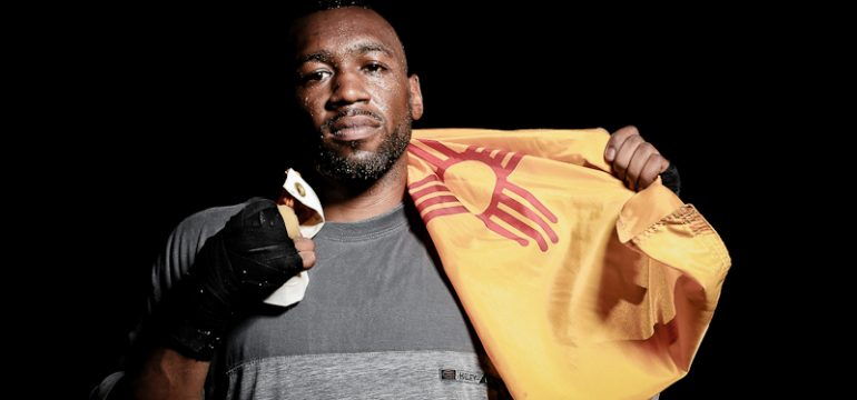 WBA Super Welterweight ChampIon Austin Trout posing with the New Mexico state flag